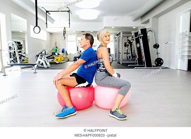 Senior man and mature woman sitting on fitness balls in gym