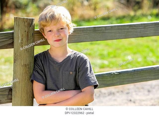 Portrait of a boy with blond hair leaning against a wooden rail fence; Oregon, United States of America