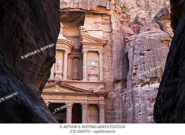 Glimpse of the façade of The Treasury (Al Khazneh) as seen through the gorge shaft (Al-Siq). Petra, UNESCO World Heritage Site, Jordan