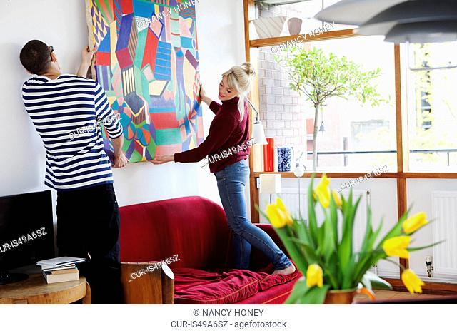 Young couple putting up painting in living room