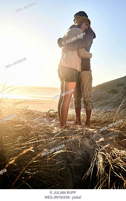 Portugal, Algarve, couple hugging at sunset on the beach