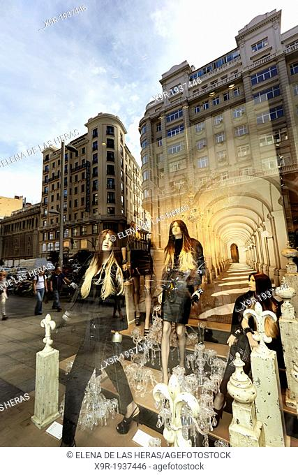 Mannequins and reflections at a window shop in Gran Via avenue. Madrid. Spain