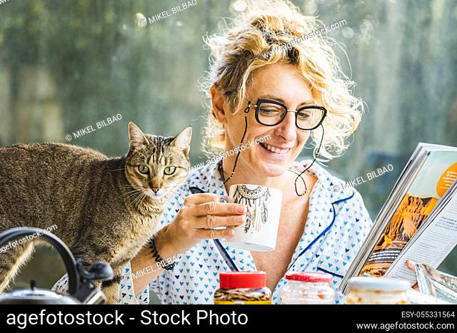 Blonde young mature woman with glasses in pyjamas at home in breakfast time, reading a magazine and having a cup of coffee and cat