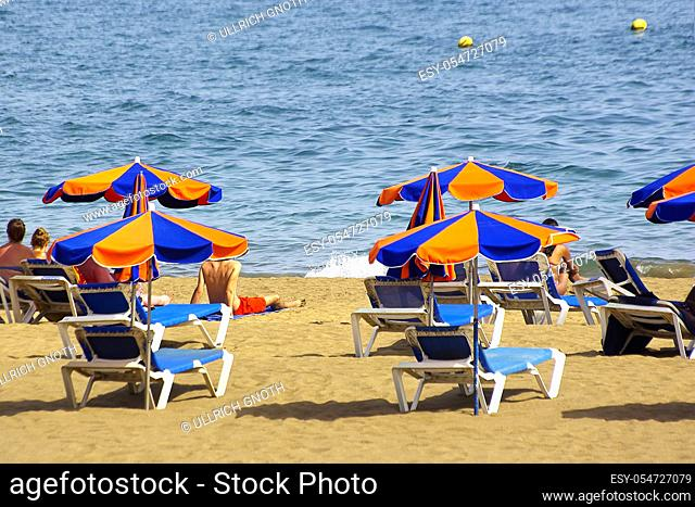 Beach scene of beach loungers and parasols on the Spanish Canarian Isla de Lanzarote and view of the Atlantic ocean