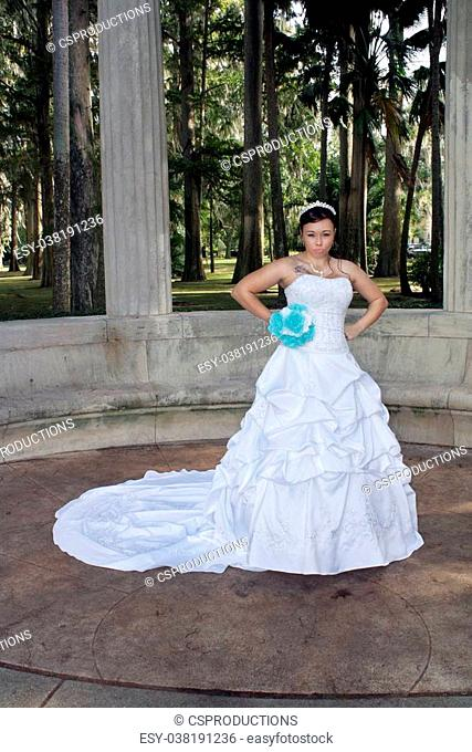 A lovely young bride outdoors wearing her wedding gown and holding her boquet, with an angry or frustrated facial expression
