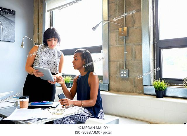 Mid adult woman showing screen of digital tablet to colleague