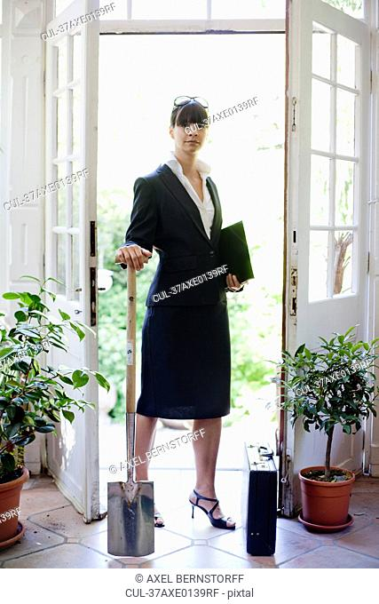 Businesswoman holding shovel indoors