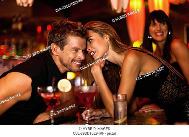 Woman whispering to bartender