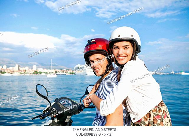 Portrait of young couple riding moped at harbour, Split, Dalmatia, Croatia