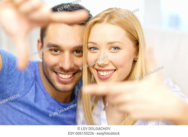love, family and happiness concept - smiling happy couple making frame gesture at home