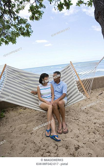 A couple sitting on hammock
