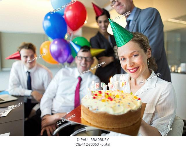 Portrait smiling businesswoman holding birthday cake with colleagues in background