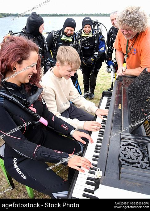 31 August 2020, Saxony, Leipzig: On the beach of the Kulkwitzer See in front of the diving school Delphin, the 15-year-old pianist Florian shows his group of...