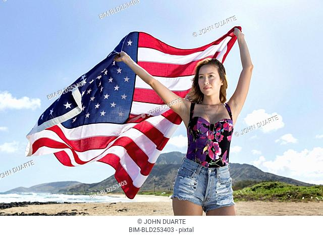 Mixed Race woman holding American flag on beach