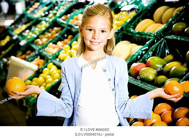Portrait of a young girl holding two grapefruits in a supermarket