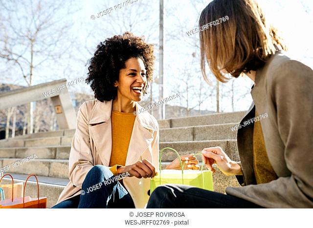 Two happy women with shopping bags sitting on stairs checking the purchase