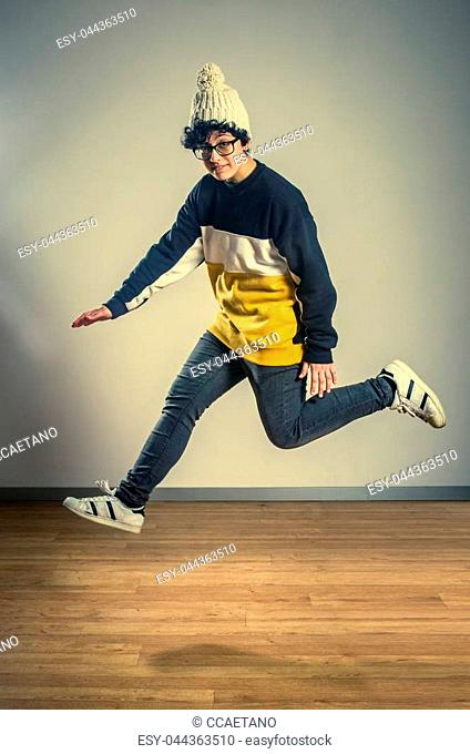 36eda8a7dab Hip Hop girl dancer wearing glasses and a white beenie hat jumping off a  wooden floor