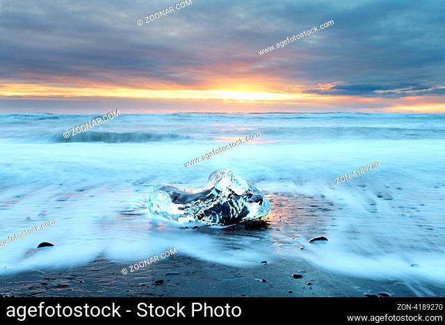 Ice on vocanic black sand iceland beach at sunset