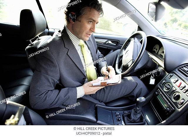 Businessman writing in car