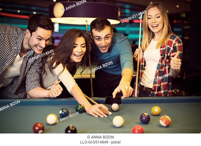 Friends cheering while their friend aiming for billiards ball. Rzeszow, Poland