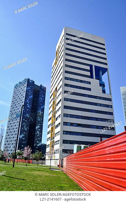 Green grass, red aluminium wall, buildings, blue sky. Plaça Europa, Plaza Europa, District VII, Gran Via, Hospitalet de Llobregat, Barcelona province, Catalonia