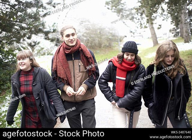 friends walking in park in winter