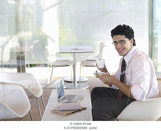 Businessman enjoying a cup of coffee in a caf+