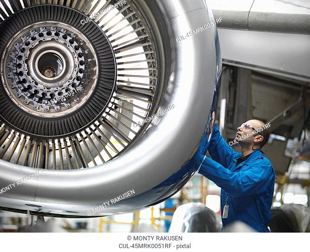 Worker examining airplane engine