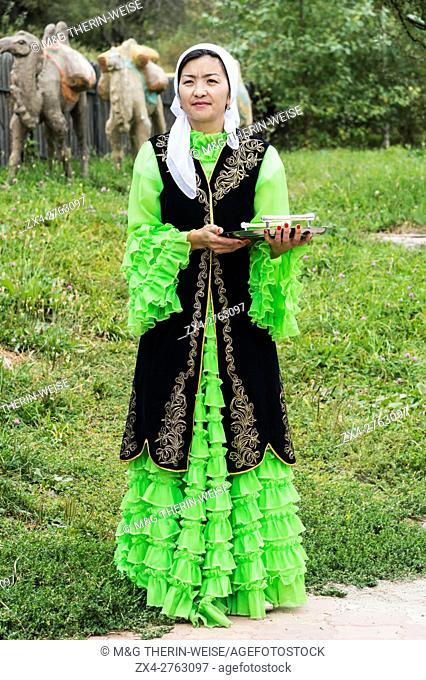 Kazakh woman meeting guests with candies, Kazakh ethnographical village Aul Gunny, Talgar city, Almaty, Kazakhstan, Central Asia, Asia, For editorial Use only