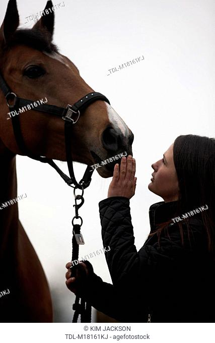 A young woman looking up at a horse, touching its nose