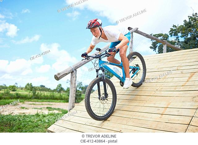 Focused mature man mountain biking down obstacle course ramp