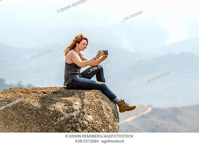 Red-headed girl sitting on the edge of a boulder taking a photo of the landscape in the Mlilwane Wildlife Sanctuary in Swaziland, Africa