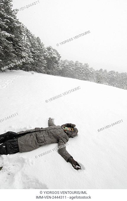 Woman lying in the snow surrounding Doxa Lake. Doxa Laka, Feneo, Corinthia, Peloponnese, Greece
