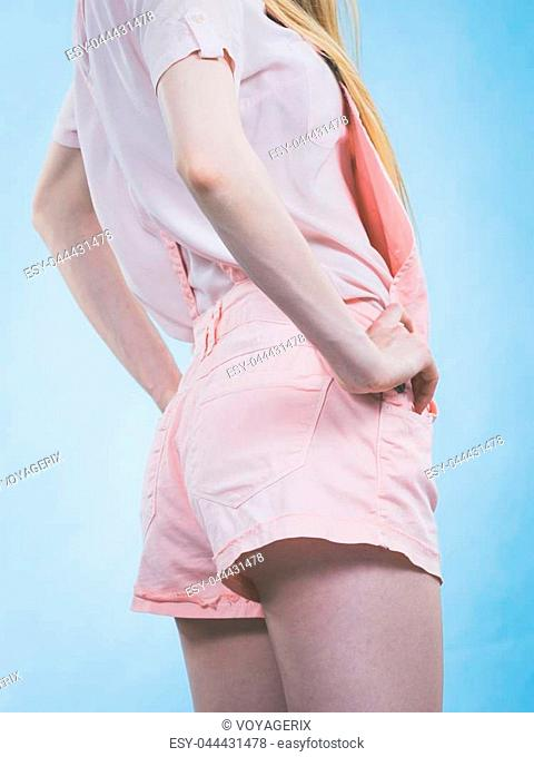 Unrecognizable woman back view. Female wearing cute outfit, pink dungarees, white tshirt. Studio shot on blue background