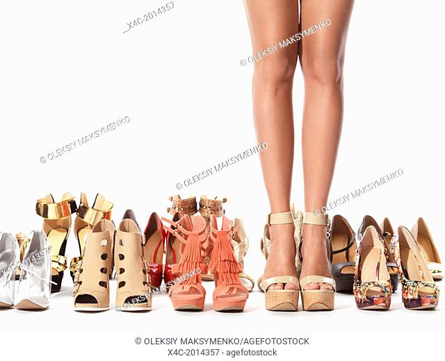 Closeup of young woman legs surrounded by several pairs of different fashionable shoes isolated on white background