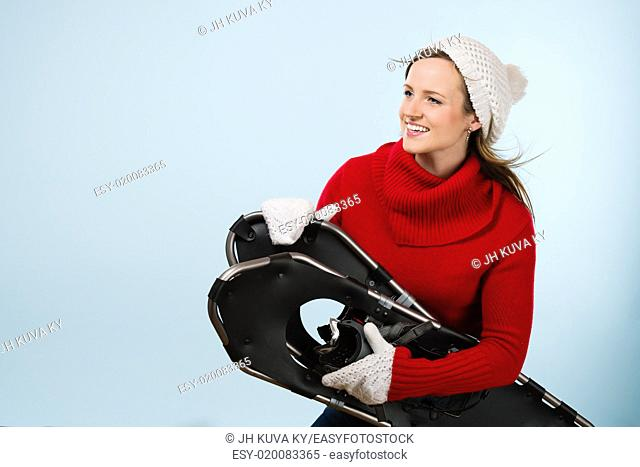 Beautiful young sporty woman with snowshoes wearing a woolen outfit, horizon format