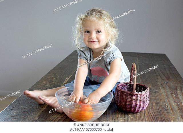 Girl rinsing vegetables in bowl