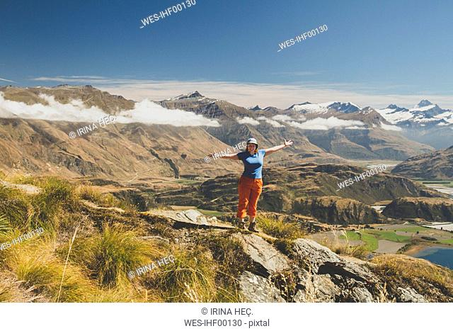 Woman standing with outstretched arms on mountain top, Roys Peak, Lake Wanaka, New Zealand