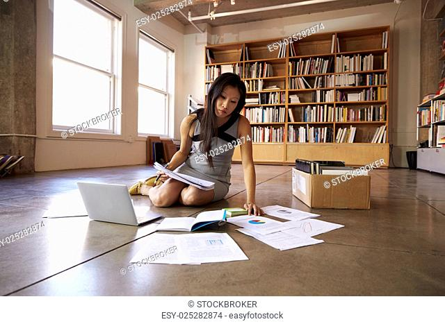 Businesswoman Laying Documents On Floor To Plan Project