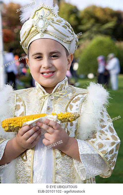 Sultanahmet. Young boy eating sweetcorn cooked on the cob wearing traditional Turkish ceremonial attire standing in front of the Blue Mosque on the day of his...