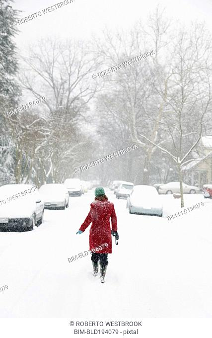 Caucasian woman walking in snow storm