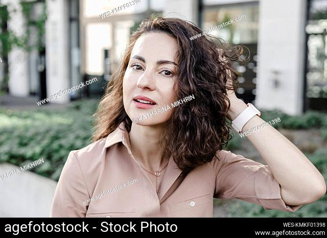 Confident businesswoman with hand In hair outside office building