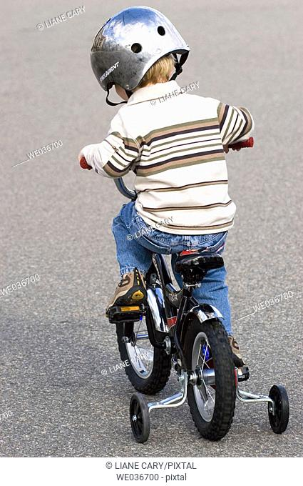 Boy riding bike with training wheels