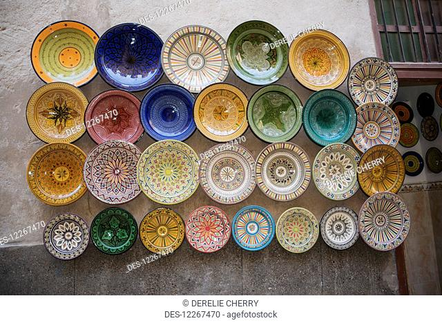 Array of beautifully designed plates for sale on wall display; Essaouira, Morocco