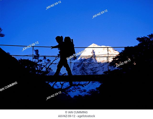 Silhouette of female hiker going across suspension bridge