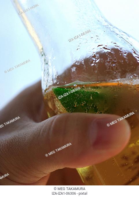 Close-up of a person's hand holding a beer bottle