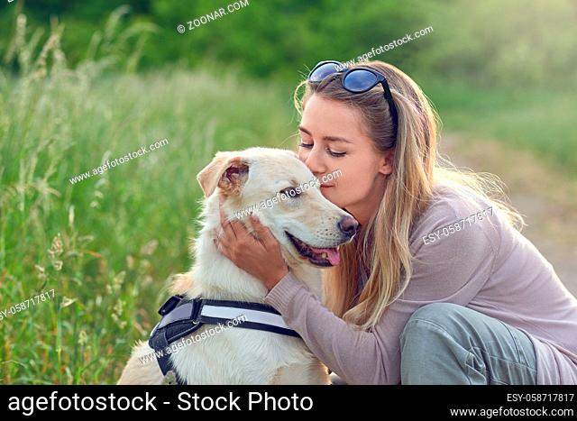 Happy smiling golden dog wearing a walking harness sitting facing its pretty young woman owner who is caressing it with a loving smile outdoors in countryside