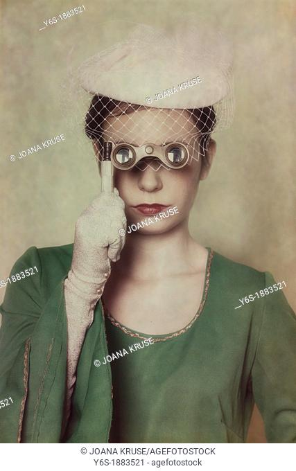 a woman in a green dress with hat is looking through a lorgnette