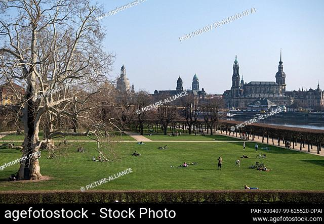07 April 2020, Saxony, Dresden: Isolated persons lie in the garden of the Japanese Palace in front of the city scenery with the Frauenkirche (l-r)
