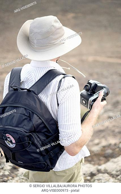 Rear View Of Man With A Camera In Hand